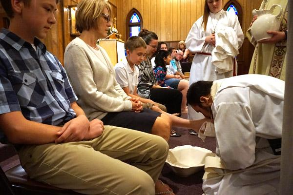 Father Rubén Quinteros, pastor at Immaculate Heart of Mary Church in North Little Rock (Marche), washes the feet of parishioner Justin Dobry, 14, during Holy Thursday Mass April 13. (Aprille Hanson photo)
