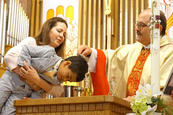 Father Norbert Rappold, pastor at St. Peter the Fisherman Church in Mountain Home, baptizes Alexander Chafin, 6, while his godmother Joanna Hill holds him up during Easter Vigil Mass April 15. (Aprille Hanson photo)