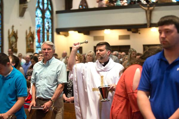 Father Jason Sharbaugh, pastor of St. Boniface Church in Fort Smith, sprinkles holy water on parishioners during Easter Mass April 16.  In all Easter Masses around the world parishioners are asked to renewal their baptismal promises. Catholics renounce Satan and promise loyalty to Christ. (Karen Schwartz photo)