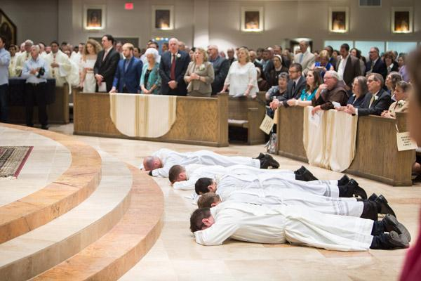 Fathers William Burmester, Stephen Hart, Ramsés Mendieta, Martin Siebold and Luke Womack lay prostrate in front of the altar at Christ the King Church in Little Rock as congregants sing the litany of the saints. (Travis McAfee photo)