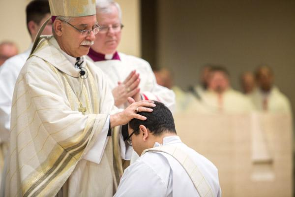 Bishop Anthony B. Taylor lays his hands on Father Ramsés Mendieta, to receive the strength of the Holy Spirit, as Msgr. Francis Malone, pastor at Christ the King Church, looks on. (Travis McAfee photo)