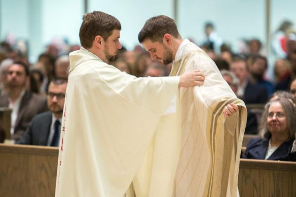 Father Andrew Hart, pastor at St. Thomas Aquinas University Parish in Fayetteville, vests his brother, Father Stephen Hart, at his priestly ordination May 27. (Travis McAfee photo)