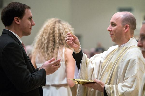Father William Burmester gives out Communion at his ordination May 27. He said seeing familiar faces in the Communion line was a special moment during the Mass. (Travis McAfee photo)