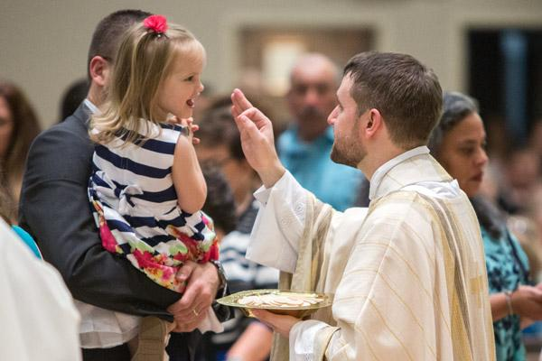 "Father Stephen Hart blesses a young girl during communion. He said his priestly ordination was the ""the beginning of the fulfillment of a calling."" (Travis McAfee photo)"
