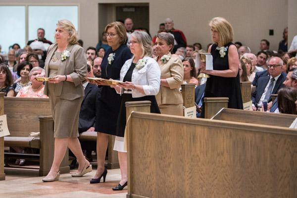 Theresa Burmester (left), Sandra Lacayo, Madelyn Womack, Evelyn Hart and Lisa Siebold, mothers of the newly ordained priests, bring the gifts to the altar during the ordination. (Travis McAfee photo)