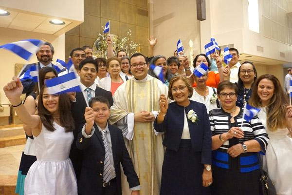 Father Ramsés Mendieta stands with his family, waving flags from his native Nicaragua following his priestly ordination May 27 at Christ the King Church in Little Rock. (Malea Hargett photo)