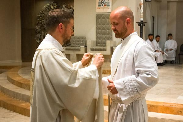 Deacon Stephen Hart, who was ordained a priest May 27, assists Deacon Patrick Friend with his stole and dalmatic. (Bob Ocken photo)