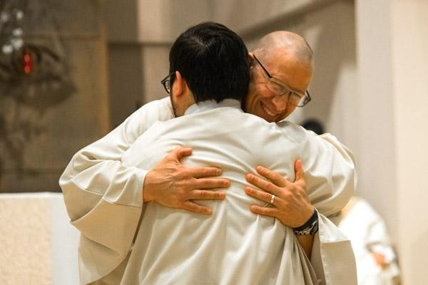 Deacon Danny Hartnedy embraces Deacon Stephen Elser during the ordination Mass. (Bob Ocken photo)