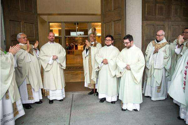 Bishop Taylor and priests applaud as the new deacons exit Christ the King Church after the ordination. (Bob Ocken photo)