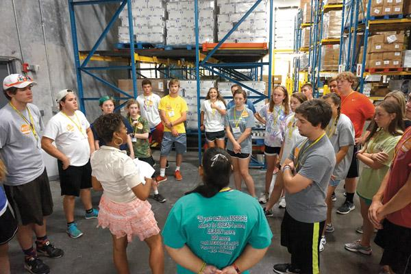 An Arkansas Foodbank staff member explains to teens attending the Catholic Charities Summer Institute how the packages they'd fill July 27 would benefit people in need. Teens attending C2SI work in service projects throughout the week. (Aprille Hanson photo)