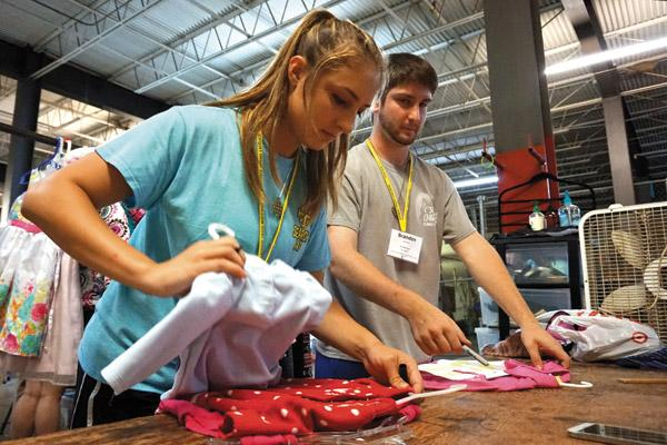 Chloe Ledbetter, 18, of St. John Church in Hot Springs, sorts children's clothes at the Little Rock Compassion Center thrift store warehouse with Brandon Locknar, 18, of St. Boniface Church in Fort Smith. (Aprille Hanson photo)