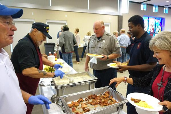 Firefighters Robert Haggard (left) and Chris Ingram are served breakfast by Knights of Columbus members at St. Mary Church during the breakfast for first responders on Sept. 11. (Aprille Hanson photo)