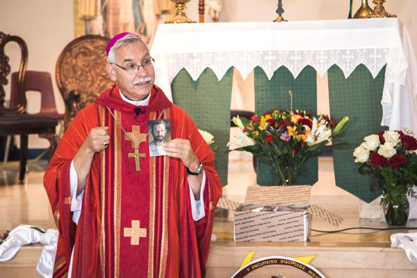 Bishop Taylor holds up a prayer card containing a small cloth that was touched to a relic of Blessed Stanley Rother. The prayer cards in English and Spanish were distributed to parishioners. (Travis McAfee photo)