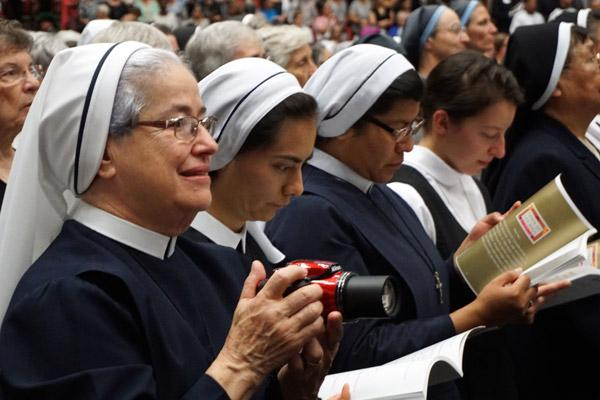 Sister Norma Munoz, diocesan director of Hispanic ministry, takes photos during the beatification Mass to share with her religious community. (Malea Hargett photo)