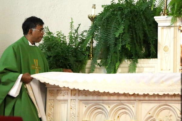 Pastor Father Alphonse Gollapalli removes items from the altar during the decommissioning Mass. (Sarah Morris photo)
