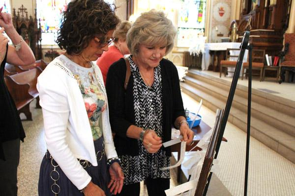 Lynn Pellegrino (left) and Denise Steinhaus of St. Mary of the Springs Church in Hot Springs tie prayer intentions to a frame before the Sept. 30 Mass. (Dwain Hebda photo)