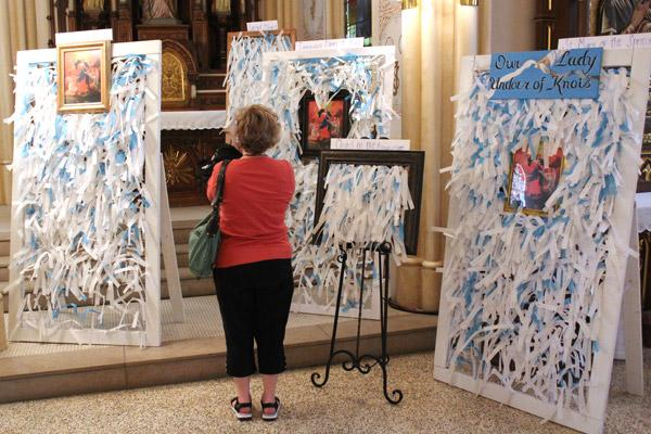Christy Miller of Our Lady of the Springs Church in Hot Springs takes a photo of panels bearing hundreds of prayer intentions to Mary Undoer of Knots. (Dwain Hebda photo)