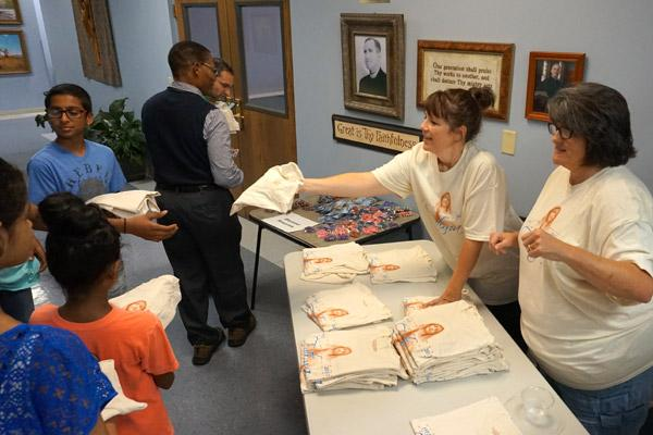 Our Lady of Fatima office manager Lori Hinojosa (left) and parish volunteer Cecelia Patton pass out Our Lady of Fatima anniversary shirts at the reception following Mass Oct. 13. (Aprille Hanson)