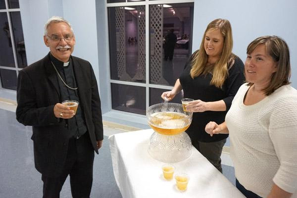 Bishop Taylor smiles as parishioners Susan Bariola (left) and Kia McGuire help serve punch in the parish hall Oct. 13. (Aprille Hanson)