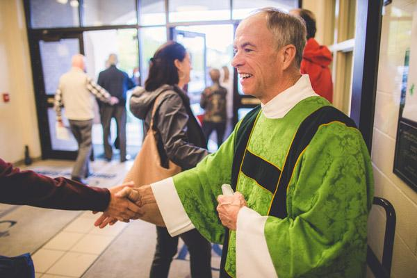 Deacon Bud Baldwin, who serves at St. Joseph Church in Fayetteville, greets parishioners following Mass Oct. 22. In September, he donated a kidney to his younger brother, Ben Baldwin of Maumelle. (Travis McAfee photo)