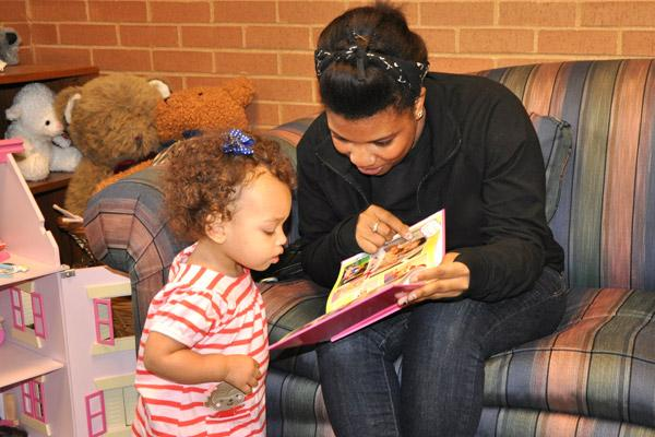 Alex reads to Olivia, then 16 months old, from a book created by her adoptive parents Rebecca and Michael that tells the story of her adoption. Alex, Olivia's birth mother, visits with the family at least once a year.