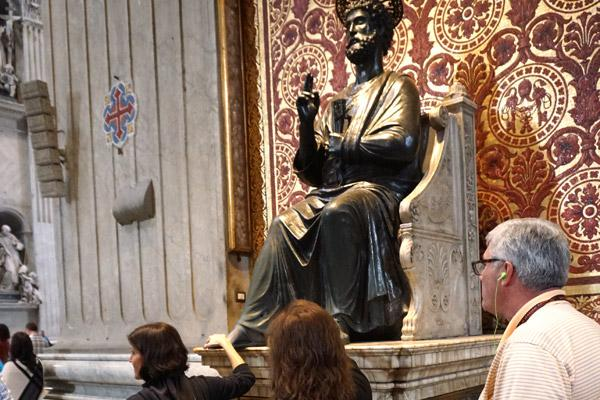 Arkansas pilgrims rub the foot of the 500-year-old bronze statue of St. Peter in St. Peter's Basilica in Rome Oct. 31. It is traditional to touch or kiss the foot when visiting the basilica. (Malea Hargett photo)