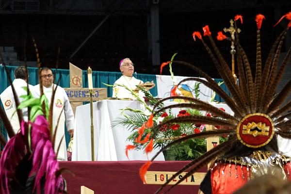 Aztec dancers stand while Bishop Taylor consecrates the bread and wine during Mass. (Malea Hargett photo)