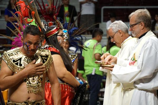 Aztec dancers receive Communion from Msgr. Scott Friend and Bishop Taylor during the Diocesan Encuentro Mass Nov. 18 at Barton Coliseum in Little Rock. (Malea Hargett photo)
