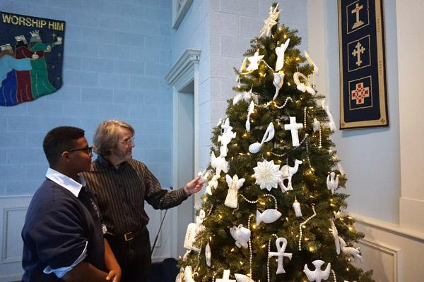 Ruskin Falls, pastor of Pulaski Heights Presbyterian Church in Little Rock, talks to his son Neil, 14, an eighth-grade student at Our Lady of the Holy Souls School, about the significance of ornaments on the Chrismon tree. (Aprille Hanson photo)