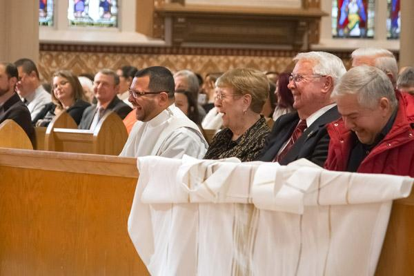 Father Rubio and the congregation laugh during a lighthearted-moment of Bishop Taylor's homily. (Bob Ocken photo)
