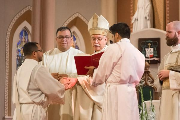 "Father Nelson Rubio makes a promise to Bishop Anthony B. Taylor of ""respect and obedience"" to him and his successors during his Dec. 16 priestly ordination. Father Juan Guido (left) served as master of ceremonies, Deacon Patrick Friend (right) was deacon of the Word and seminarian Jaime Nieto assisted the bishop. (Bob Ocken photo)"