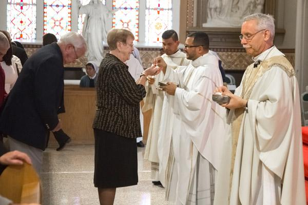 Father Rubio gives communion to Sue Wood of St. John Church in Hot Springs. Dennis and Sue Wood, parents of Father Mark Wood, sat with Father Rubio during the Dec. 16 ordination. (Bob Ocken photo)
