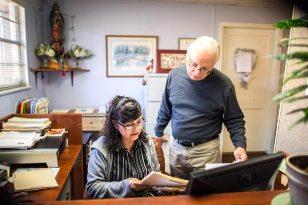 Catholic Charities Immigration Services - Springdale secretary Alma Beltran (left) and director Frank Head look at client records in January. Government application fees for many immigration processes jumped at the start of 2017. (Travis McAfee photo)