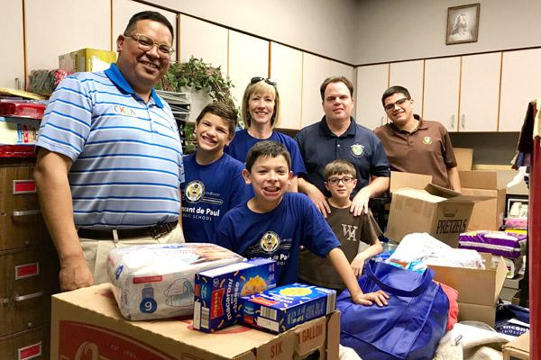 Principals John Rocha (left) and Alice Stautzenburger (center), along with St. Vincent de Paul Rogers students Thomas and Gabriel Rocha, oversee a collection of Hurricane Harvey donations to faculty, staff, families and friends of Western Academy in Houston in September. The donations were given to academy teacher Mike McManus and his son Peter. Stephen Rocha (right), a Western Academy graduate, joins them. (File photo)