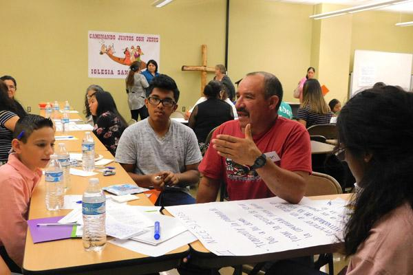 As part of the nationwide V Encuentro initiative, Juan Manuel Ruiz, a member of St. Edward Church in Little rock, speaks to a group, including Gustavo Villarruel (far left) and teenager Alejandro Marquez during their Parish Encuentro Sept. 30. Arkansas had 30 parish teams evangelizing within their communities since Oct. 2016. (File photo)