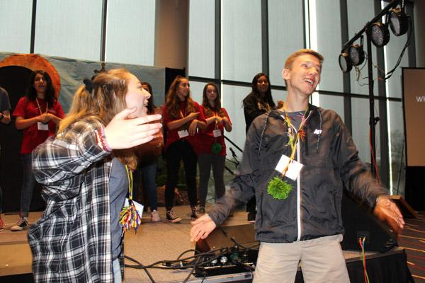 Youth Advisory Council members Claire Hollenbeck of Fort Smith and Collin Gallimore of Hot Springs get attendees up and dancing during Saturday morning activities during the state youth convention. (Dwain Hebda photo)