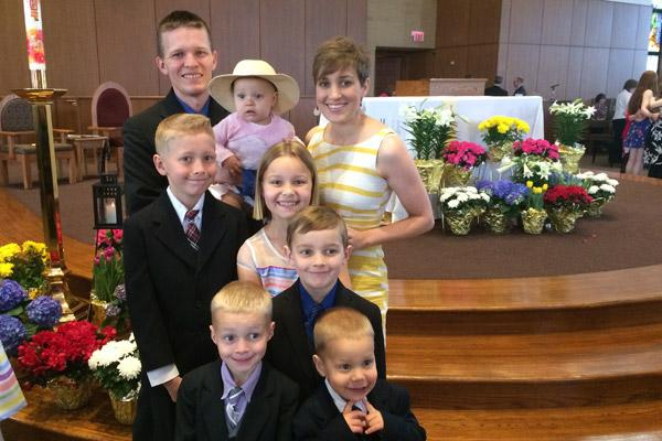 Jason and Erin Pohlmeier hoist Faustina, 1, as they gather their children in Easter finery for a photo at St. Joseph Church. They are (middle row left to right) Isaac, 11; Clare, 10 and Dominic 7. Front row left to right are Vincent, 5 and Damien, 3.