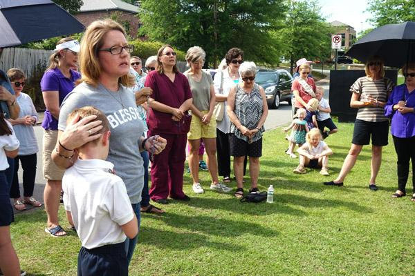 Lori Wilbur prays the rosary as her son Solomon, 7, rest his head against her. She along with her husband Lee, vice president of the Arkansas Pregnancy Resource Center board of directors, organized a rosary outside the center, less than 24 hours after it burned down. (Aprille Hanson photo)