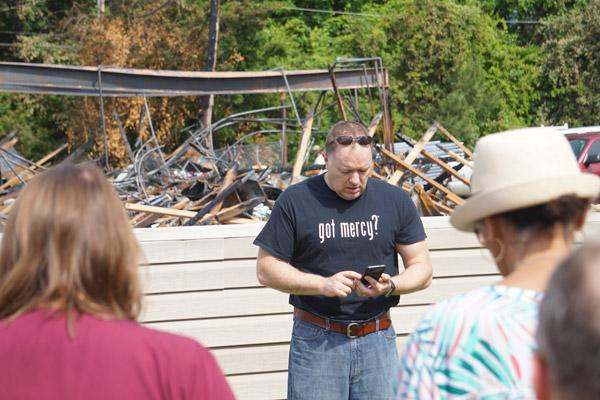 Lee Wilbur, vice president of the Arkansas Pregnancy Resource Center board of directors, reads the rosary mysteries from his phone, leading the prayers in front of the burned center. (Aprille Hanson photo)