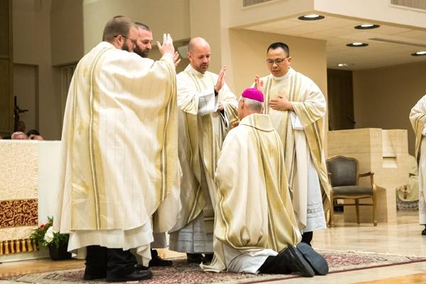 Fathers Keith Higginbotham, Jeff Hebert, Patrick Friend and Tuyen Do bless Bishop Anthony B. Taylor before the end of Mass May 26. (Bob Ocken)