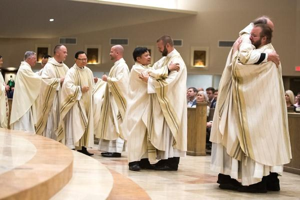 Diocesan priests line up to hug and congratulate their new brother priests during the sign of peace. (Bob Ocken)