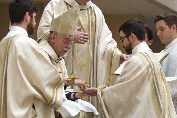 Bishop Taylor anoints the hands of Father Joseph de Orbegozo with chrism oil June 2. (Bob Ocken)