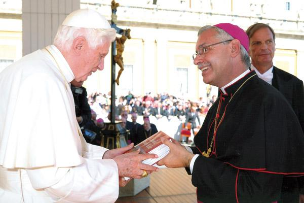 While in Rome for the diaconate ordination of then-seminarian Andrew Hart, Bishop Anthony B. Taylor attends the general papal audience Oct. 5, 2011, and gives Pope Benedict XVI a hardback copy of the new Little Rock Study Bible, which was first published that summer by Little Rock Scripture Study. (Courtesy L'Osservatore Romano)