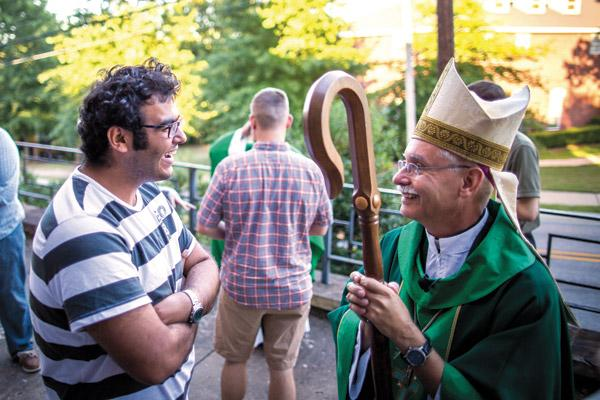 Egyptian student Wassim Khalil, 22 (left), stops by after Mass at St. Thomas Aquinas University Parish in Fayetteville to chat with Bishop Anthony B. Taylor Sept. 18, 2016. The conversation began in English and finished in French, a second language the two share. (Travis McAfee / Arkansas Catholic file)