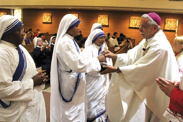 Sister Maria Jyoti hands Bishop Anthony B. Taylor the decanter of wine flanked by her fellow Missionaries of Charity Sisters during Mass for St. Teresa of Kolkata Sept. 4, 2016, at Our Lady of Good Counsel Church in Little Rocks. (Dwain Hebda / Arkansas Catholic file)