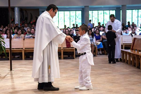 "Angelo Figueroa, then 8 years old, receives first Communion from Father Juan Manjarrez at St. Vincent de Paul Church in Rogers in 2014. Right after receiving Communion, Figueroa, who was born with a brain disorder called agenesis of the corpus callosum, joyfully said ""I got it,"" Debbie Dufford said, who helps prepare those with special needs for the sacraments. (Paul Dufford photo)"