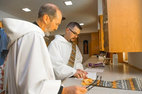 Before their priestly ordination, Benedictine Brothers Reginald Udouj and Cassian Elkins look over the Mass program July 14 at St. Benedict Church at Subiaco Abbey. (Bob Ocken photo)
