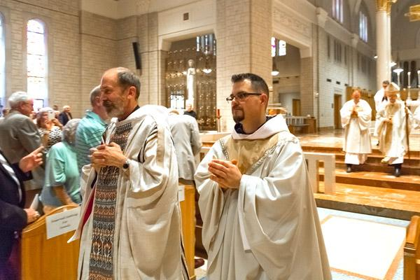 Fathers Reginald Udouj (left) and Cassian Elkins process out of St. Benedict Church at Subiaco Abbey following their ordination Mass July 14. (Bob Ocken photo)
