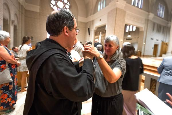 Father Cassian Elkins' longtime friend Maria Annis, who is deaf and blind, uses an interpreter to express her joy of being present at his ordination. Father Elkins, who previously worked as a professional American Sign Language interpreter, hopes to continue ministry with the deaf community. (Bob Ocken photo)