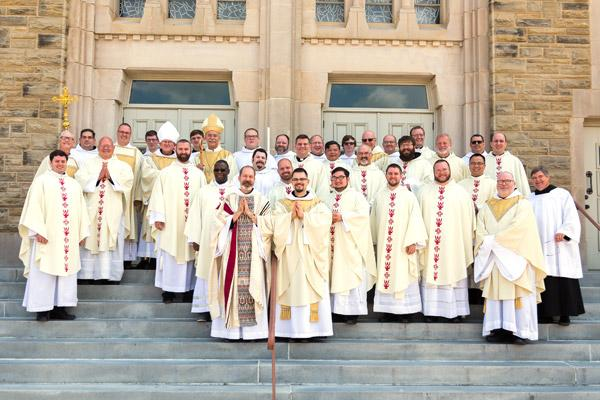 Newly ordained Fathers Reginald Udouj (front left) and Cassian Elkins pose with Bishop Anthony B. Taylor, Abbot Leonard Wangler and fellow priests following their ordination July 14. (Bob Ocken photo)